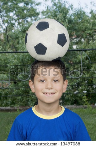 Young cute boy holding a soccer ball over his head