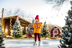 Young cute boy in orange winter jacket and red hat holding Santa's cup of cacao with marshmallows standing on a fake ice rink among Christmas trees.