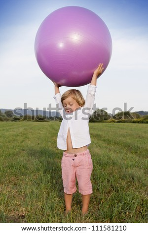 Young cute boy playing outdoors with big medicine fit ball