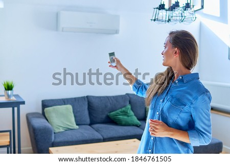Young cute casual woman using air conditioner and adjusting comfortable temperature with remote control at apartment Foto stock ©