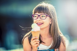 Young cute caucasian blond girl with dental braces glasses and ice cream.