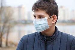 Young cute caucasian boy wearing protective mask against the corona virus on the street. Teenager in surgical  face mask to prevent from virus Covid 19 in the city.  Close up portrait