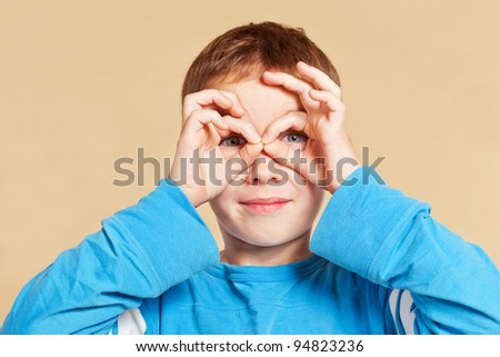 Young cute caucasian schoolboy making a telescope with his hands looking into the camera. Youth concept.