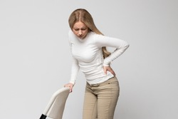 Young cute Caucasian woman having pain, muscle or chronic nerve pain in her back, hold the chair/Health Issue, diseases of musculoskeletal system concept/Diseases of spine, scoliosis, osteoporosis