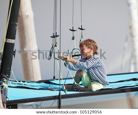 young cute child boy on sea catamaran / yacht