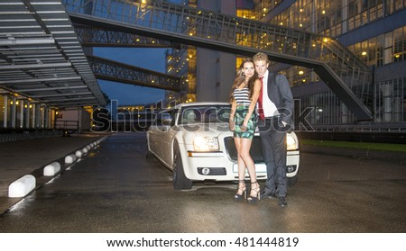 Young, cute couple, standing in front of a strech limousine in a retro looking industrial facility