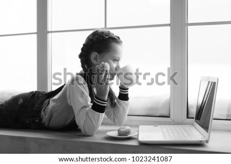 Stock Photo Young cute emotional teenager girl with braids in overalls lies by the window indoor. With cup and cookies, working with the laptop. Monochrome