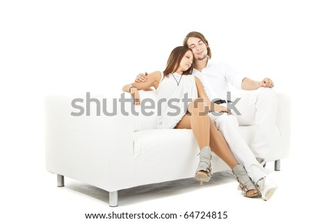 Young cute european couple om a white couch - isolated over white.