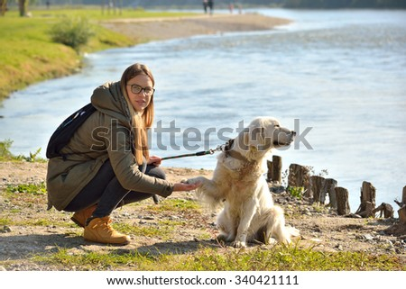 young  cute girl holding paw of ...