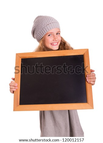 Young cute girl holds a small blackboard and is smiling into the camera
