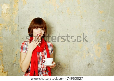 Young cute girl in a checkered red dress against a background of an old concrete wall drinking coffee from a white cup
