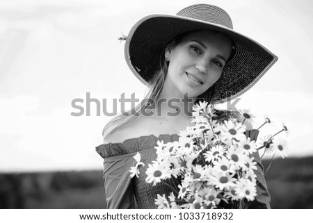 Young cute girl in a hat in a village field at sunset #1033718932
