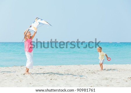 Young cute girl playing her brother with a colorful kite on the tropical beach.