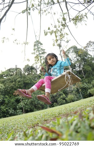 Young cute girl playing swing in the park.