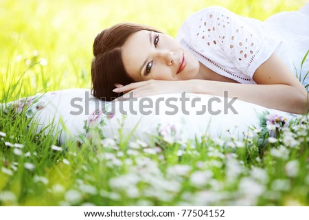 stock photo : Young cute girl resting on soft pillow in fresh spring grass