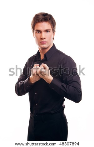young cute guy keeps his fists threatened in the studio on a white background
