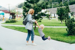 Young cute mom twirls her little adorable daughter in the city park. Emotions of a mom fooling around with a little daughter. A family walk together, happy, carefree moments. Parenting.
