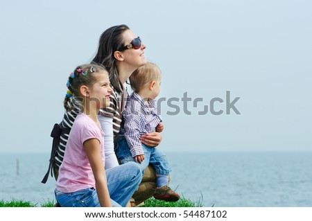 Young cute mother with a daughter and son looking at the sea