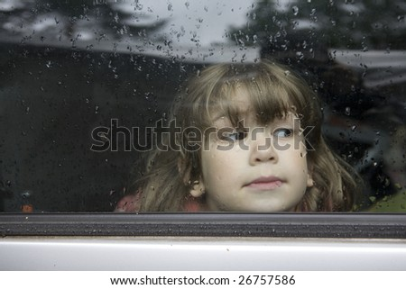young cute pensive girl looking through window of car. Window covers of rain`s drops