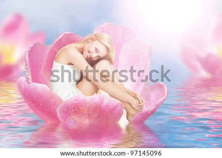 Young cute woman as thumbelina sitting in tulip