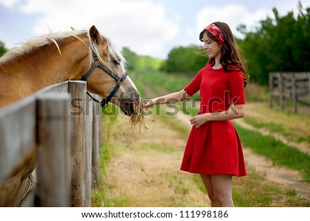 Young cute woman feeding horse on farm
