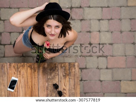 Young cute woman with black hat and flower Portrait of lady from above vanishing point in black unusual hut top brassier holding rose flower between her breasts colorful stone paving road background