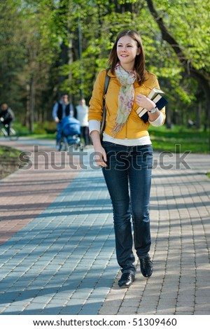 young cute woman with books walking in the park