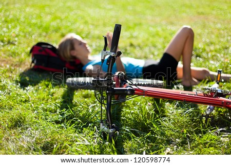 Young cyclist enjoying relaxation lying in the fresh green grass illuminated by the rays of sunlight. Outdoor