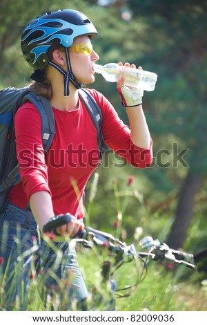Young cyclist on a mountain bike drinks water