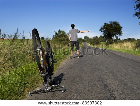 young cyclist wating for a car on the road
