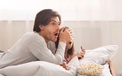 Young Dad And His Little Girl Are Watching Horror, laying on bed and eating popcorn, father closing daughter eyes, copy space