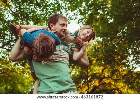 young dad playing with his  active children in the garden