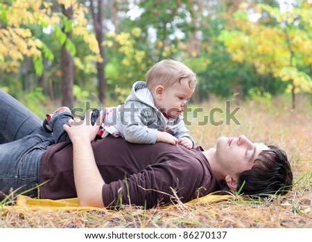 young dad playing with son on autumn outdoor