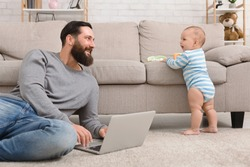 Young dad working on laptop and taking care of his baby son, enjoying paternity leave, free space