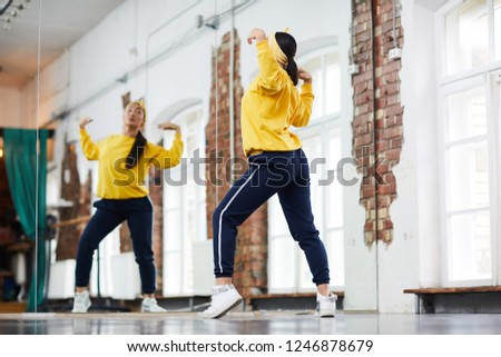 Young dancer in activewear training in front of large mirror in studio of modern dancing