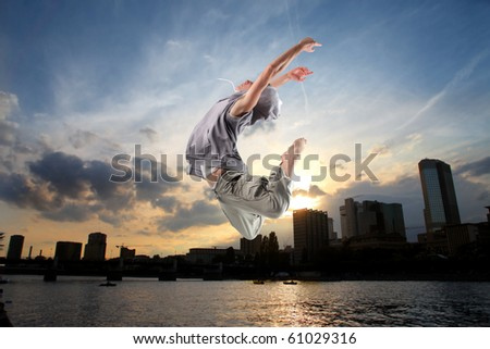 Young dancer jumping with cityscape at sunset on the background