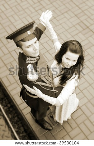 Young dancing couple on rialroad station in old-fashion costumes