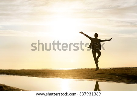 Young dancing girl silhouette in sunbeam at sunset on the beach. Vibrant outdoors horizontal image. Baltic sea coast. #337931369