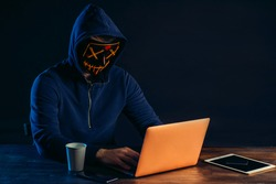 young dangerous hacker bandit engaged in crime, don't afraid of strangers, entered the room and hack laptop system, password. cyberattack nowadays. isolated in dark space