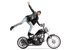 Young daredevil standing on the seat and riding a chopper motorbike isolated on white background