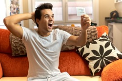 Young dark-haired man in white t-shirt and gray tracksuit celebrating that he has won the lottery. Teenager looking at a paper and being surprised on orange sofa with cushion and window