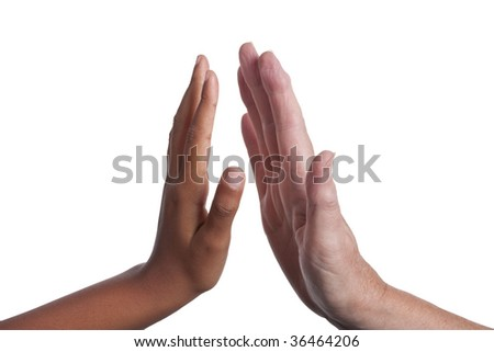 Young dark skinned mixed race girls hand, giving a High Five to an  older fair skinned senior woman's hand. Isolated on white background including clipping path.