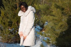 Young dark-skinned woman in a white fur coat among pine trees in winter.