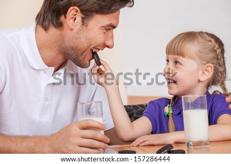 Young daughter is feeding her father with chocolate cookies - stock photo