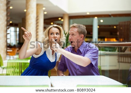 Young debating or talking couple inside mall sitting near the table