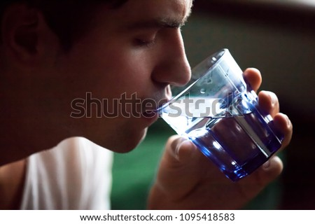 Young dehydrated man drinking filtered mineral clear water quenching thirst, thirsty guy holding glass hydrating for body refreshment and energy recovery, hydration and health concept, close up view