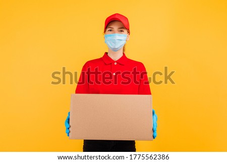 young delivery girl in a red uniform, wearing a medical mask and gloves, holds a cardboard box isolated on a yellow background. Delivery service, quarantine, coronavirus