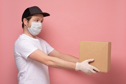 Young delivery man in medical mask holding and carrying a cardbox isolated on pink background
