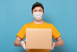 Young delivery man in nedical mask holding and carrying a cardbox isolated on blue background. Buy food online in quarantine concept.