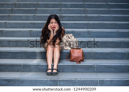 young depressed and desperate Asian American business woman crying alone sitting on street staircase suffering stress and depression crisis being victim of mobbing or fired losing her job #1244900209